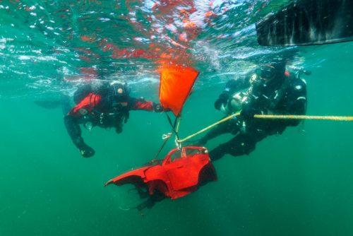 Duikers halen auto onderdelen van speelgoedauto's uit zee
