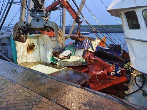 Bergingsboot met containerresten en ander afval